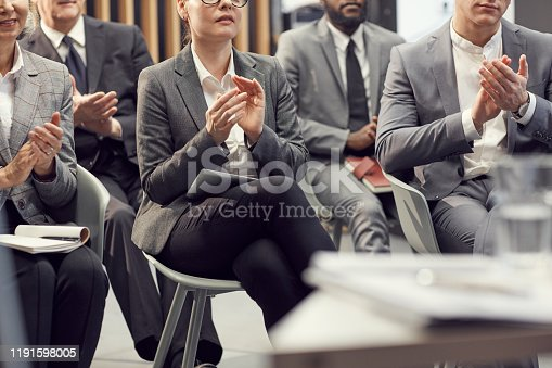 862720340 istock photo Close-up of business audience sitting on chairs and clapping hands to speaker at conference 1191598005