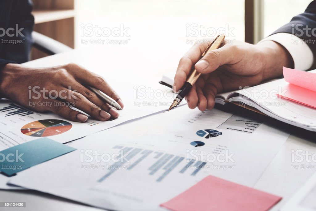 Close-up of business man and partner hands pointing at business document while discussing it royalty-free stock photo