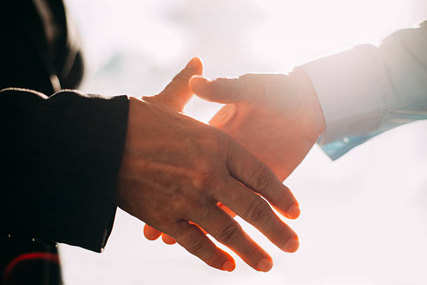 Close-up of business people hands shaking Close-up of male and female hands shaking. Business people greeting with handshake dignity stock pictures, royalty-free photos & images