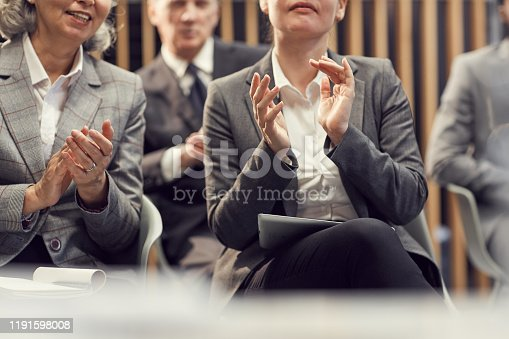 862720340 istock photo Close-up of business people in formal jackets sitting in auditorium and clapping hands while welcoming coach at training class 1191598008