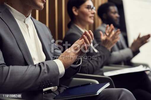 862720340 istock photo Close-up of business people in formalwear sitting with notepads in row and applauding speaker at business conference 1191598248