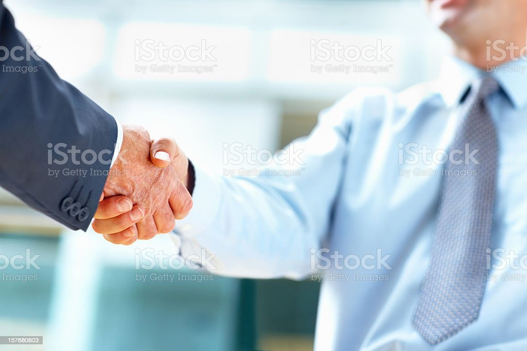 Closeup of business people shaking hands over a deal royalty-free stock photo