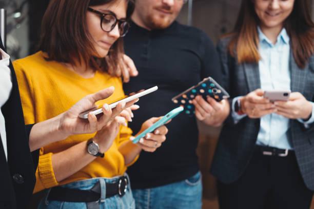 Nahaufnahme von Geschäftsleuten, die zusammenarbeiten und modernes Smartphone im Büro nutzen. Digitale Gadgets mit Konzept – Foto