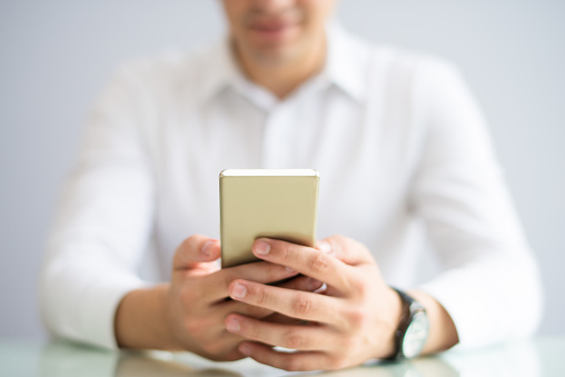 istock Close-up of businessman browsing internet on smartphone 1056270052