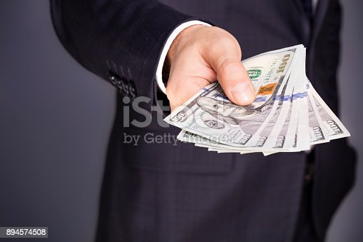 istock Closeup of businessman giving a stack of money 894574508