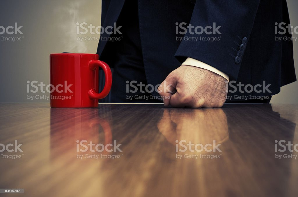 Close-up of Businessman Hitting Desk with Fist Beside Coffee Cup royalty-free stock photo