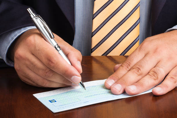 Closeup of businessman or salesman hand writing signing blank check stock photo
