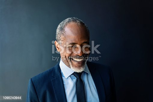 istock Close-up of businessman smiling against wall 1095240944