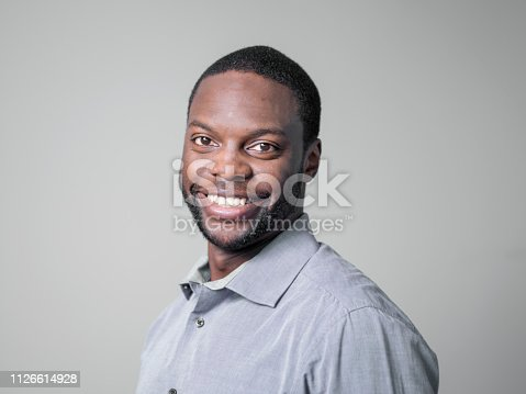 istock Close-up of businessman smiling on gray background 1126614928