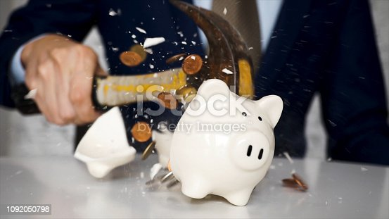 istock Close-up of businessman using a hammer to smash plenty of coins inside piggybank into pieces as he needs emergency money - using money in financial crisis concept. 1092050798