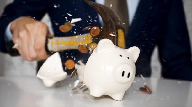 close-up van zakenman met behulp van een hamer smash allerlei munten binnen spaarpot in stukken zoals hij noodgeld moet-met behulp van geld in het begrip van de financiële crisis. - gebroken stockfoto's en -beelden