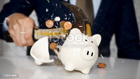istock Close-up of businessman using a hammer to smash plenty of coins inside piggybank into pieces as he needs emergency money - using money in financial crisis concept. 1132519491