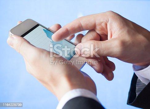 826058232istockphoto Closeup of businessman using a smartphone 1164225739