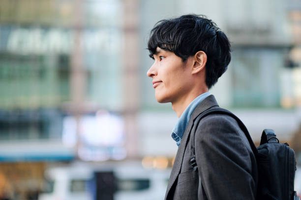 Closeup of businessman walking on street Asian young businessman walking on street japanese ethnicity stock pictures, royalty-free photos & images