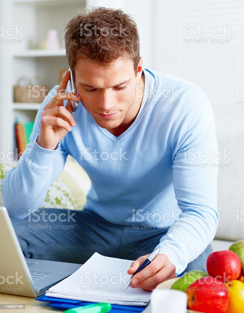 Close-up of businessman working and talking on cellphone at home stock photo