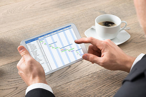 Close-up Of Businessman Working On Digital Tablet Close-up Of Businessman Working On Gantt Chart On Digital Tablet At Desk In Office gantt chart stock pictures, royalty-free photos & images
