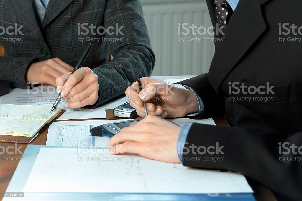 Close-up of businessman's hands making notes, mobiles, chart, desk, office royalty-free stock photo