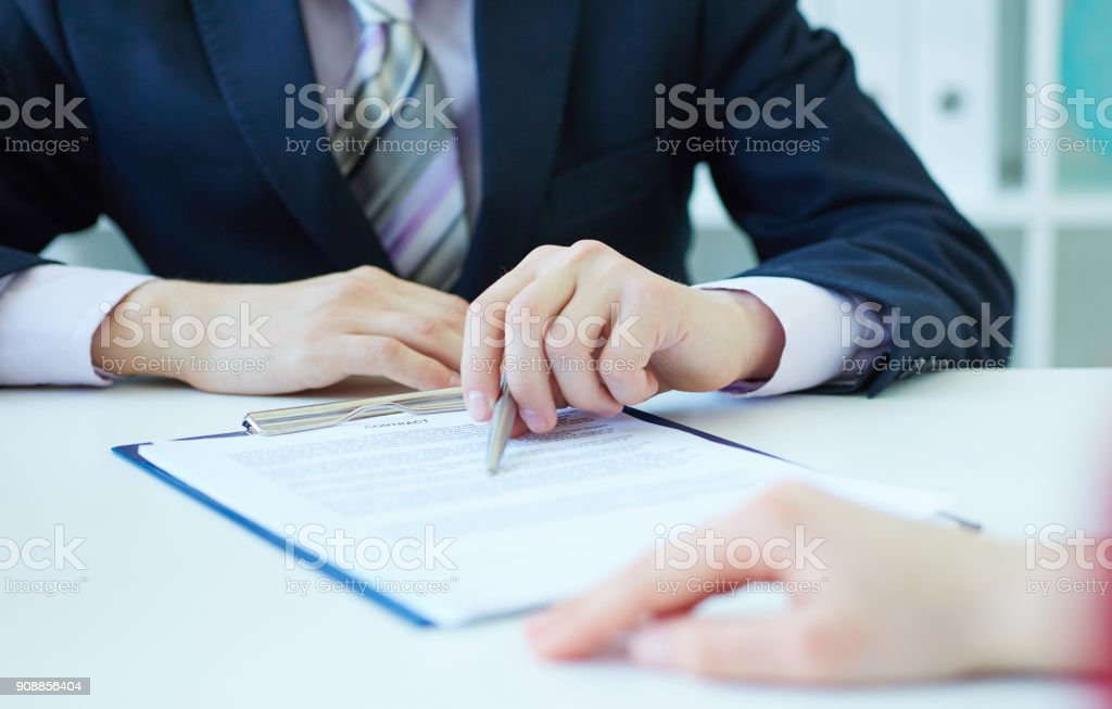 Closeup of businessman's hands showing  his new business partner the terms of the agreement or contract. Selective focus. Selective focus. stock photo