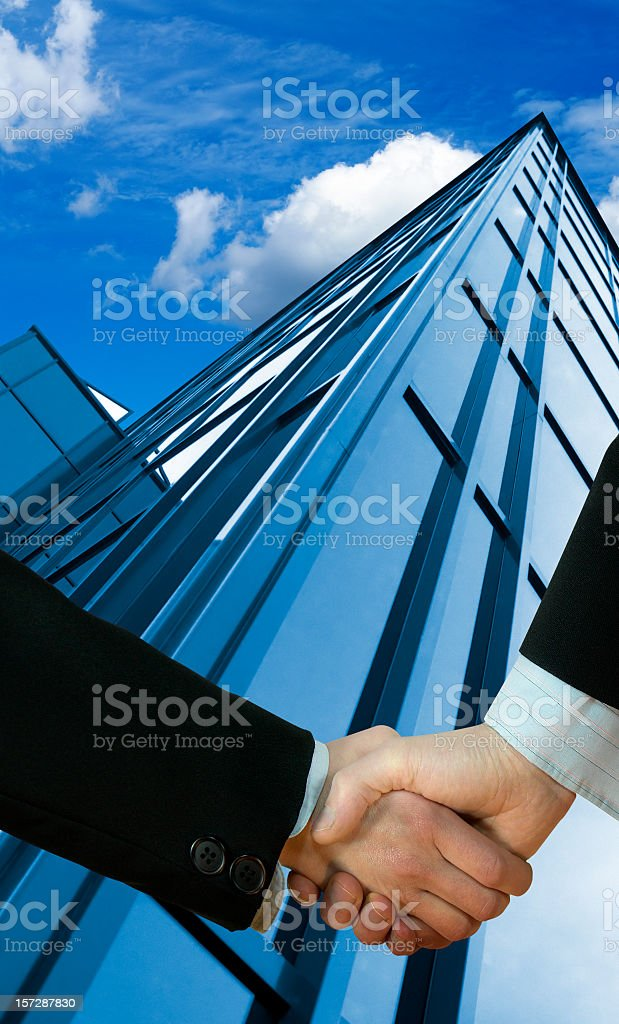Close-up of businessman's handshake against blue skyscrapers and blue sky royalty-free stock photo