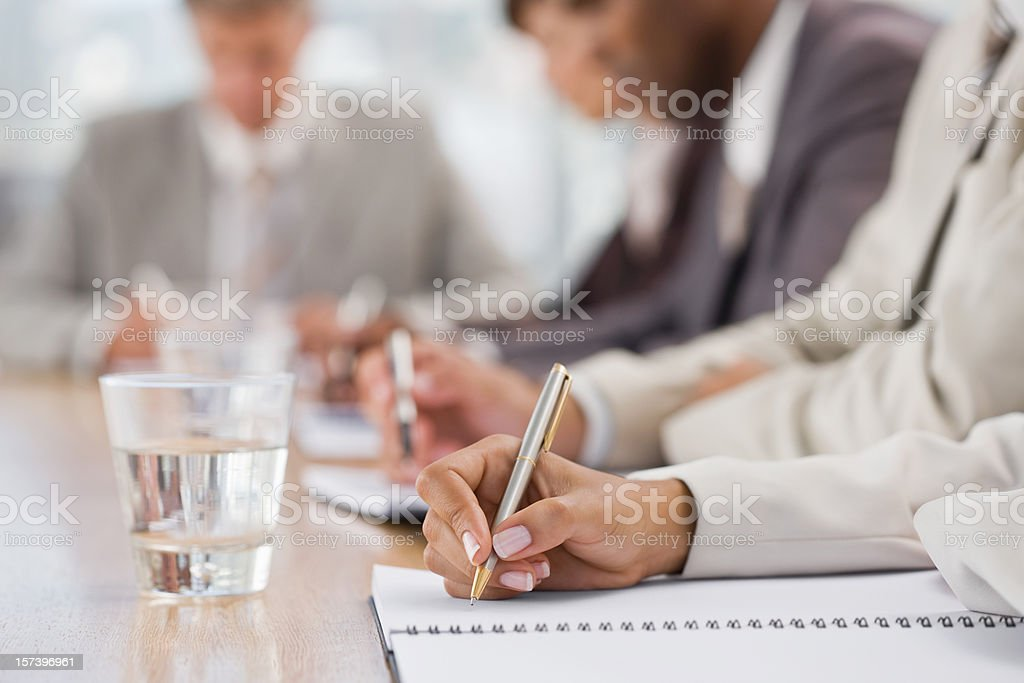 Closeup of businesspeople writing royalty-free stock photo