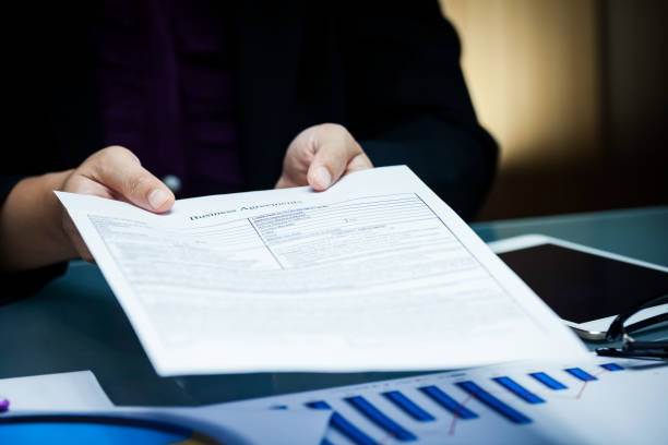 Close-up of businessperson give agreement document with graph data document on desk stock photo