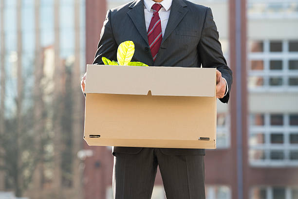 close-up of businessperson standing with cardboard box outside o - ausscheiden stock-fotos und bilder