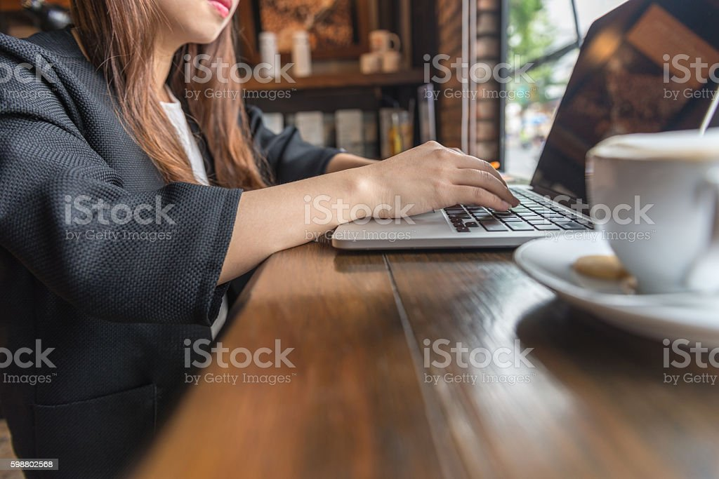 Close-up of businesswoman hand typing on laptop at cafeteria stock photo