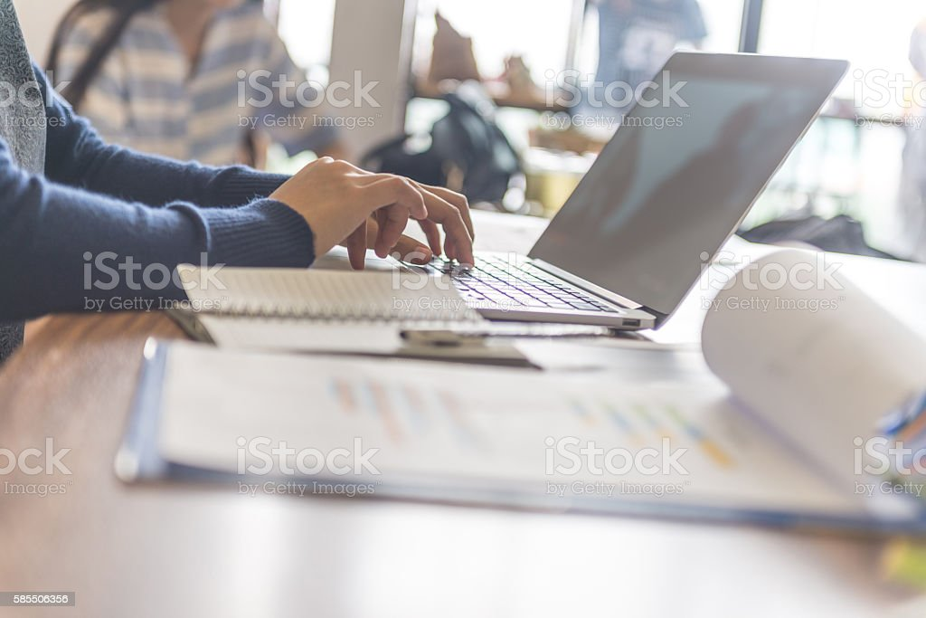 Close-up of businesswoman hand typing on laptop at workplace stock photo