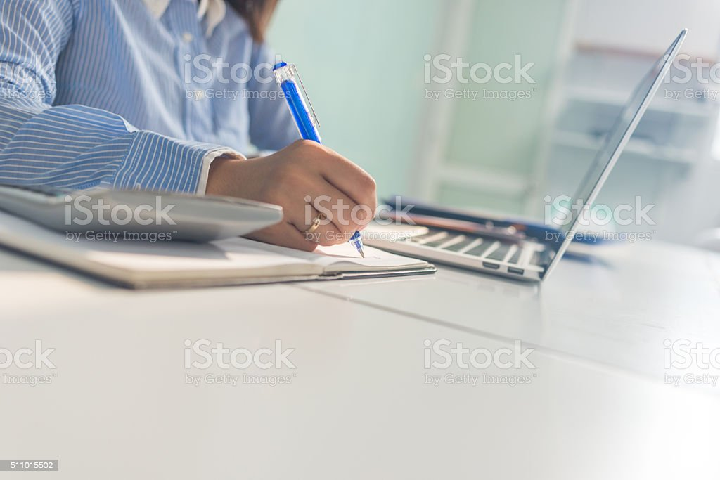 Close-up of businesswoman hand writing notes in her office stock photo