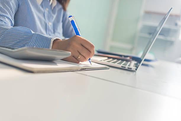 cerrar de mano de mujer de negocios escribir notas en su oficina - clase de escritura fotografías e imágenes de stock