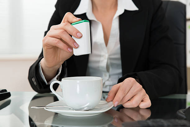 close-up of businesswoman putting sugar in cup - sweeteners stock photos and pictures