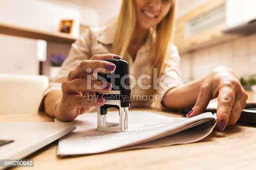Close-up of businesswoman working in the office and stamping files.