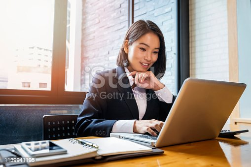 Closeup of businesswoman using laptop at office desk. She searching web or browsing information.