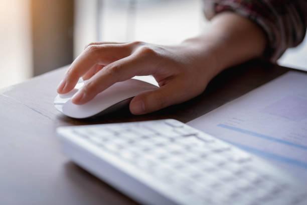 nahaufnahme der geschäftsfrau hand hält eine computer-maus. technik im büro. - computermaus stock-fotos und bilder