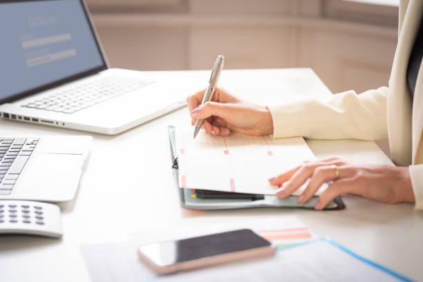 Nahaufnahme der Hand der Geschäftsfrau beim Noten auf dem Notizbuch – Foto