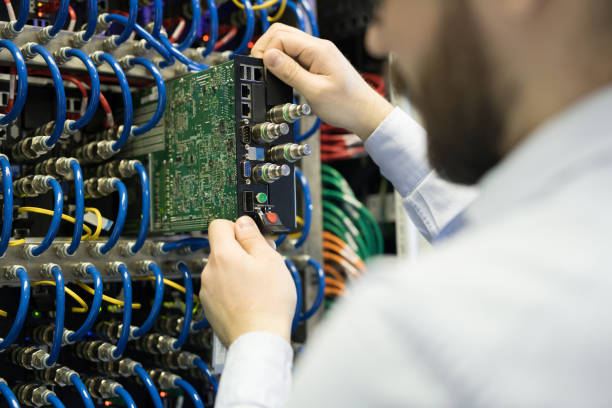 Close-up of busy technician installing hard drive in server rack cabinet to improve speed of supercomputer at mining farm stock photo