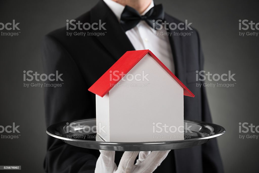 Close-up Of Butler With House Model stock photo