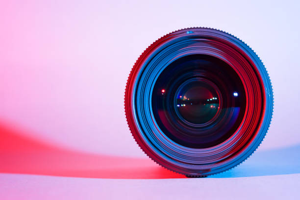 closeup of camera lens with red and blue lighting - camera lens stock photos and pictures