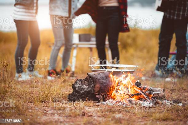 Photo of Closeup of campfire with friendship dancing to beat of the music for celebrating in party with mountain meadow and lake view background. People lifestyle and travel vacation. Picnic and camping tent