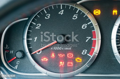 Closeup of car tachometer with many illuminated indicators