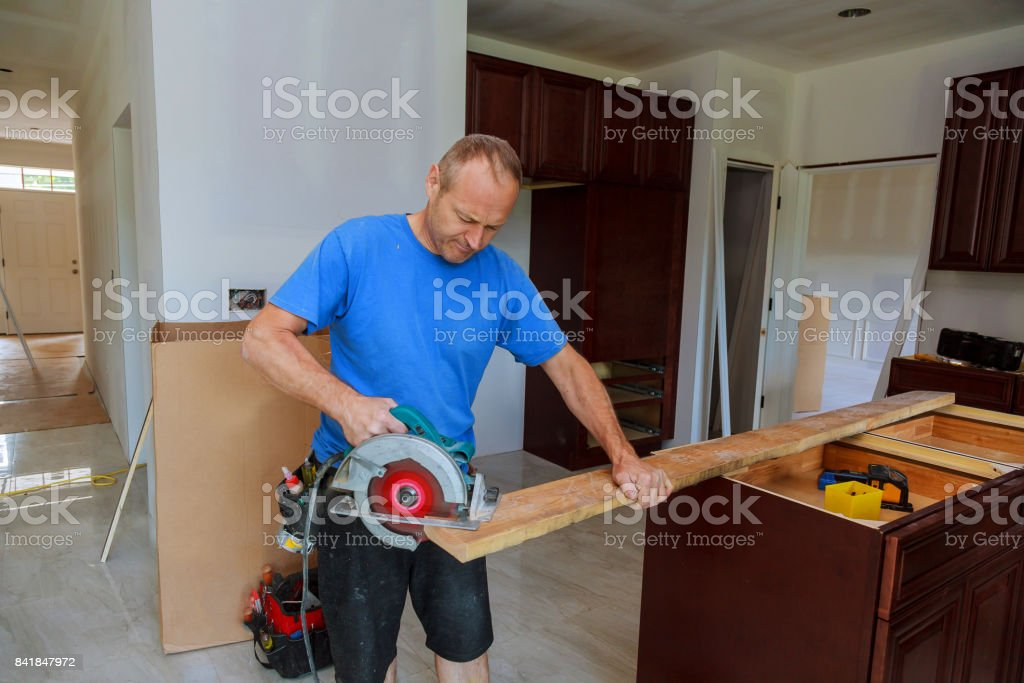 Close-up of carpenter using a circular saw to cut a large board of wood stock photo