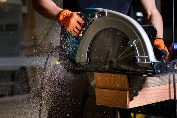 nahaufnahme der tischler mit elektrischen kreissäge holz planken geschnitten - tischlerarbeit stock-fotos und bilder