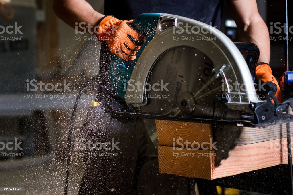 Close-up of carpenter using electric circular saw to cut wood planks stock photo