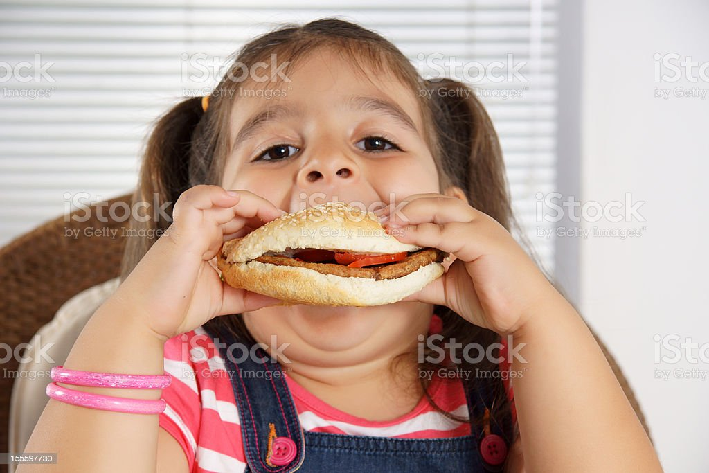 Close-up of Caucasian girl with pigtails eating a burger stock photo