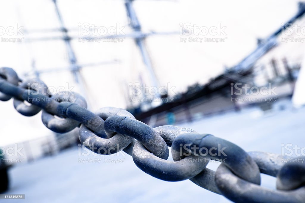 Close-up of chain with tall sailing ship in background. Docks. stock photo