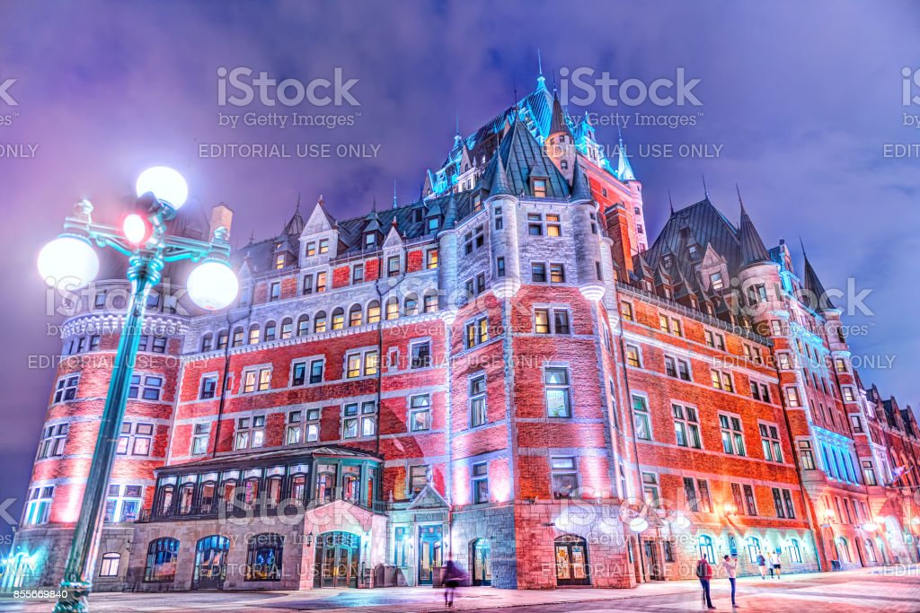Closeup of Chateau Frontenac castle hotel in old town at night, with evening lantern or lamp, people, square stock photo