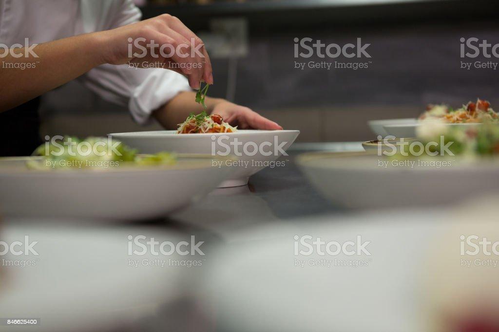 Gros plan du chef garnir les repas sur le comptoir - Photo
