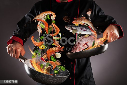 Closeup of chef throwing sea fruit and fish into the air, fire flames around. Concept of food preparation