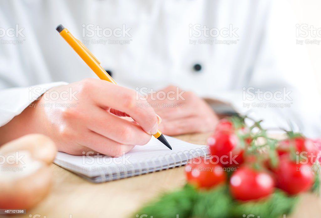 Close-up of chef writing in a notebook stock photo