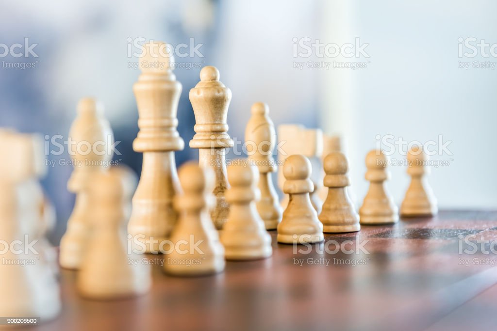 Closeup of chessboard with wooden pieces on table in sunlight, soft bokeh stock photo